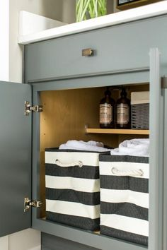 Striped baskets help organize the large lower cabinet below that also includes a shelf for laundry cleaning products.