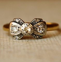 1920's Platinum Diamond & 18k Gold Ribbon Bow Ring is absolutely stunning. The band is plain & smooth 18k yellow gold and the platinum setting is in a ribbon bow shape. The setting measures 6mm x 1.2cm wide set with three 2.5mm beautiful sparkling round diamonds across the center and four tiny diamonds on the edges of the 'ribbon'- I believe one of these was replaced as it's slightly larger than the others a couple are cloudy but they are so small it is hard to tell. $365.00