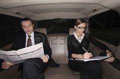 Zaken man lezing krant zaken vrouw schrijven op een organisator in de auto Stockfoto