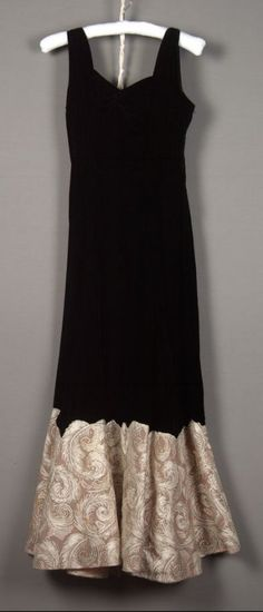 Evening dress Date: ca. 1935–1940 Media: Black Velvet,gold Metallic Lace Accession Number: 1983.63.8 Sleeveless full length dress. Black Velvet with sweetheart neck, flared skirt with deep scalloped hem border of gold feather design lace mounted on horsehair. No label.
