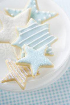 Galleticas de estrellas decoradas con estos modelos y colocadas en la bandeja de vidrio blanca con detalles dorados.para mesa.