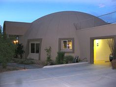 Image: Garage – A rectangular, stucco 4-car garage is attached to the dome-home.