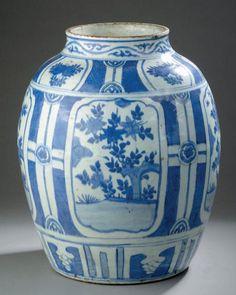 Grande jarre en porcelaine bleu blanc. Chine, dynastie Ming, époque Wanli (1573-1619). De forme ovoïde, la panse divisée en quatre panneaux ornés de fleurs et arbustes fleuris, entrecoupés de motifs géométriques, l'épaulement décoré de cartouches de fruits, le col de rinceaux. (fêle au col et usures à l'émail). H. 44 cm