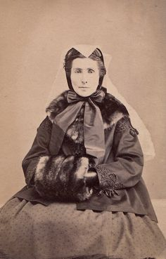 The sitter is wearing a short sackcoat with beading and a dark printed dress, black gloves, a large fur muff, and a matching stole. She is wearing a nice bonnet with silk ribbons and a white crape veil over the bonnet and pinned. These never caught on in the U.S. and were mainly used in England for second mourning, 1863.