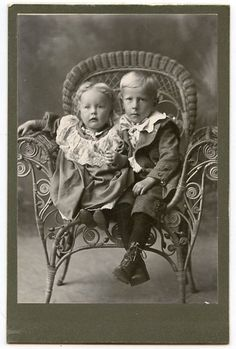 Vintage photo of two cute children.  Look at that chair.  I have an old antique similar.  I have no idea of its age