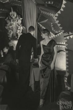 Schiaparelli dress at the Shéhérazade    In this beautifully composed photograph, a model is shot in the famed Parisian nightclub Shéhérazade. She wears an asymmetrical, one-shouldered evening dress by Elsa Schiaparelli. Donald Honeyman's image appeared in the October 15, 1949, Vogue.