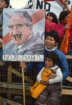 """Mother and child with an anti-Pinochet poster saying """"No to the Devil"""" during the '""""No"""" referendum campaign. """"Pinochet was campaigning in civilian clothes (although he was a general) because he wanted to show that he was a nice guy. So at the anti-Pinochet rallies, they used the pictures he was using in his campaign for the 'Yes' vote and just painted in the horns of the devil. Julio Etchart"""