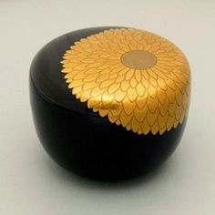Japanese lacquered tea box or caddy (Usucha-ki or natsume)  for holding the powdered tea used in traditional tea ceremony, gold chrysthanthemum decoration on black, lacquered wood
