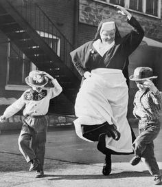 A nun dances a highland fling with a couple of young cowpokes. Like ya do.