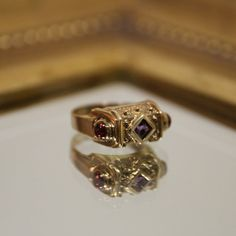 This eye-catching etruscan style ring is set in 14K yellow gold. Intricate texture and detailing is common with Etruscan jewelry. The princess cut amethyst is bezel set and makes an attractive center point with 2 garnet cabochons flanking the sides.  Details: Metal: 14K Yellow Gold Weight: 4 grams TGW Stones: Amethyst (1), Garnet (2) Size: 5 US  ► Custom Ring Sizing Available CLICK HERE! https://www.etsy.com/listing/484718316/custom-ring-sizing?ref=shop_home_act...