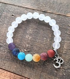 Matte Gemstone Chakra Bracelet with Crystal Quartz and Om charm - Wear the Rainbow! Matte gemstone chakra gemstones paired with matte genuine rock crystal quartz.  Rock crystal quartz has the wonderful quality of amplifying the qualities of gemstones it is paired with, which means that it makes other gemstones stronger and more powerful! #chakrabracelet