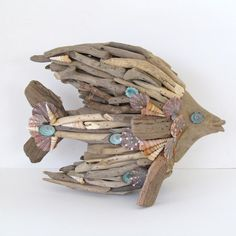 Driftwood Sculpture Fish Angelfish Shells. I created this driftwood fish sculpture using lots of weathered driftwood pieces, calico shells, turquoise limpit shells and .tan turetella shells. His eyes are turquoise limpits with dark umboniums. This piece is about 11 inches long and 8.5 inches high. Would be great in any coastal decor and comes from a smoke free home. Will be very carefully packaged for shipping.