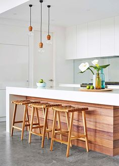 Here, the timber fascia, stools and light fittings give this kitchen truly standout looks – the woven seats add texture and the subtle touches of colour in the glassware are soft and inviting | Home Beautiful Magazine Australia