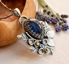 Silver Botanical Necklace with Kyanite, 18 carat gold and topaz.