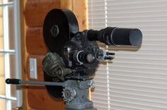 Bell & Howell 71-Q Eyemo 35mm motion picture camera with the 400ft film magazine and motor attached on a tripod.