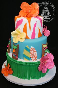 Luau-themed party cake covered and decorated with fondant.  All decorations you see - masks, surf boards, flowers, and grass skirt - are edible!