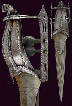 Indian Vijayangara katar, 17th century, triangular double edged blade with raised grooves on both sides and strengthened tip; iron grip with a large knuckle-guard strengthened by toothed bands pierced at the borders and the centre, the pommel shaped as a stylized dragon head with parry ring; lateral bands with riveted mounts, pierced at the centre, undulated at the borders and engraved with geometrical motifs; two cross-bars with oval knots at the centre.