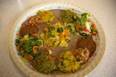 four vegetarian stews and two salads, served on a bed on injera bread.