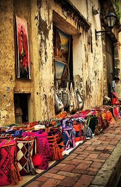 A Moroccan artisan's street display of his handmade colorful bags, somewhere in Tangiers, Morocco.