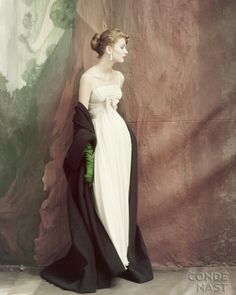 Photo by John Rawlings: Suzy Parker wears a strapless white chiffon empire waist dress, the waist banded with rhinestones, paired with an emerald green cloak by Gunther Jaeckel.  This appeared in the October 15, 1953 Vogue.