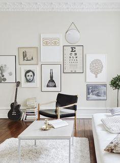 Sala de estar em tons claros e com galeria de posters