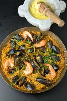 Fideus noodles are first browned in olive oil, then simmered in a rich fish and shellfish broth and topped with mussels and shrimp.