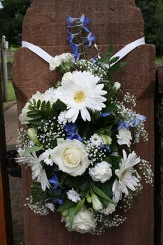 Church Wedding Flowers. White Gerbera, Roses, Alstomeria, Carnations, Gypsophila & Blue Delphinium arranged on a batton holder and hung on the Stone Gate post at the Church entrance. By H J Strike.