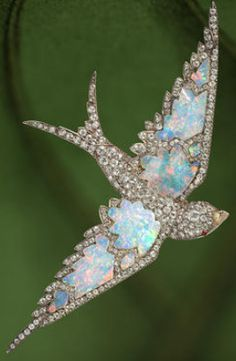 An antique opal and diamond swallow brooch, circa 1870. Pavé-set with diamonds, centring free-form opals, enhanced by ruby cabochon eyes; retailed by Garrard, with signed box; estimated total diamond weight: 4.25 carats; mounted in silver-topped fourteen karat gold; length: 4in. (pin stem is detachable)