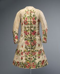 Waistcoat, early 18th century, British. The plain white linen of this striking waistcoat was quilted and embroidered with exotic flora in polychrome silk and metallic thread. The climbing vines and vibrant flowers recall the popular Tree of Life motif associated with Indian palampores. The small-patterned flat quilting that decorates the linen ground, common to English bedcovers and garments of the period, also offers evidence of Indian influence. The yellow silk thread on the ivory ground…