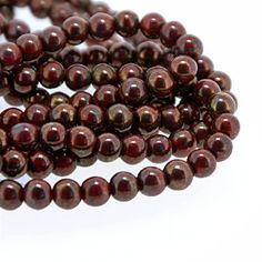 5-06-P915696.  High quality premium Czech Glass beads.  Opaque Dark Red with a Bronze picasso coating.  Measures 6mm diameter with a 1mm hole.  Pack