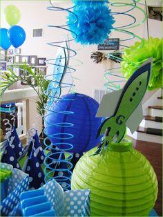 Globos verde, morados y blancos y pantallas de papel, Naves espaciales y cintas de regalo del mismo color para la decoración.