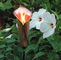 Calla Lily design holds a removable oil lamp for beautiful illumination at night.  6 ft. stake lets you place it in a flower border or in landscaping. Flower is copper plate on brass. Oil holder is copper plate on stainless steel.