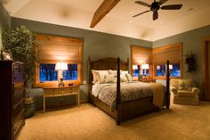 Custom master bedroom design with large wood bed, wooden blinds and green walls