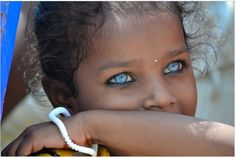 """Varanasi's Eyes"", Photo & caption by Raquel Escudero: ""The intensity of a city in the eyes & skin of a little girl""; Varanasi, India."