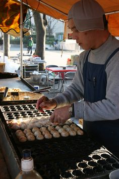 "Japanese Street Food ~ Takoyaki ~The word ""tako"" means octopus, and ""yaki"" means grilled, which means takoyaki are grilled octopus balls. Bite-sized pieces of boiled octopus are placed in the half-spherical mold of a takoyaki pan, and then a batter mixed with dashi, tempura pieces, and green scallions is poured over. As the batter cooks, it is turned over and it puffs up to form a ball."