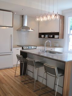 cuisine - Ranger. Classic modern kitchen. White cabinets, walnut accents, wood floors, marble counters, open shelving, hexagonal tile.