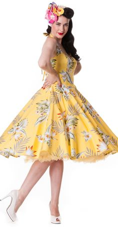 A yellow coloured 50s dress with a full circle skirt, halterneck ties and an all over tropical Hawaiian print featuring hibiscus flowers and palm leaves. The fabric in the bust has been carefully sewn to create a unique and subtle shape. The back of the dress has an elastic smocked panel to give a snug fit.
