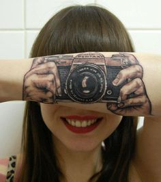 Brunssum, Netherlands-based tattoo artist Helma van der Weide created this optical illusion tattoo for her daughter Lotte van den Acker's forearm. All Lotte needs to do to show off her passion for photography is cover up her eyes with her arm and voila! Instant photography!