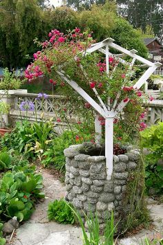 A quaint garden wishing well that includes a rose arbor. Another sweet way to get roses up out of the reach of browsing deer.