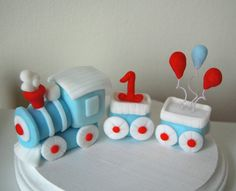 Make this adorable trains next trip to the top of your cake! This train is made with modeling fondant and comes with a number and balloons. This set would be the perfect size for an 8 inch cake. Order as is, or customize it and choose your own colors, number, and balloons! If you want other items placed in the carriages let us know! We would love to make it even more personalized. *Prices may vary depending on amount of customization* Some colors are prone to fading if your item is made w...