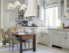 Kasler reinvents the eat-in kitchen by mixing formal Louis XV-style dining chairs — played down in Donghia's Relaxed Linen in Storm —  with a 19th-century French farm table and silver-leaf Capucine chandelier from Niermann Weeks. The Roman shade in Galbraith & Paul's Zinnia in Sky is another curveball. Frances Janisch  - HouseBeautiful.com