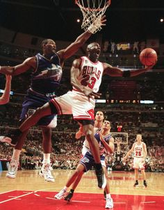 The Chicago Bulls' Michael Jordan goes up and under Utah Jazz forward Karl Malone as he drives to the hoop during the third quarter of Game 2 in the NBA Finals on June 4, 1997, in Chicago. (Tribune file photo)