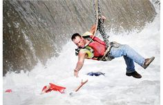 A construction worker suspended from a crane, rescues a woman who fell into the Des Moines River near the Center Street Dam in Des Moines, Iowa in this July 1, 2009 photo. This image by Des Moines Register photographer Mary Chind won the 2010 Pulitzer Prize for Breaking News Photography.