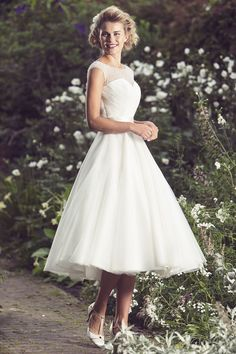 Elegant wedding dress features illusion beaded overlay on the strapless sweetheart bodice topped by a-line tea length organza skirt.