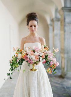 Romantic garden-style floral arrangement, designed in a gold pedestal bowl. #wedding #centerpiece