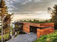 modern split level built into the mountainside with horizontal wood exterior and a flat green roof