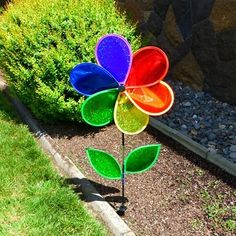 "19"" Rainbow Glitter Flower with Leaves.  Add sparkle to any space! Made with quality Mylar material and fiberglass frames, this 19 inch Rainbow Glitter Flower with Leaves comes with a fiberglass pole and ground stake. Easy assembly with a pre-assembled Petal Wheel. #glitter #flower #spinner"