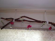 Kleine vaasjes met ijzerdraad in takken gehangen met nep bloemetjes