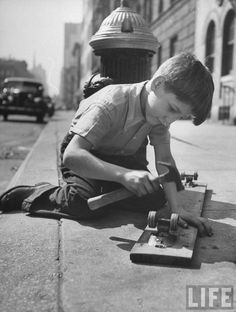 Young boy nailing wheel parts from an old roller skate to a wooden plank in the first step toward making an orange crate scooter. New York, 1947.  By Ralph Morse
