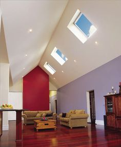An expansive living room with a tall cathedral ceiling. In one side of the ceiling, three roof windows provide light to the room. Roof Ceiling, Ceiling Lights, Passive Design, Roof Window, Aluminium Windows, Visual Comfort, New Homes, Skylights, Living Room